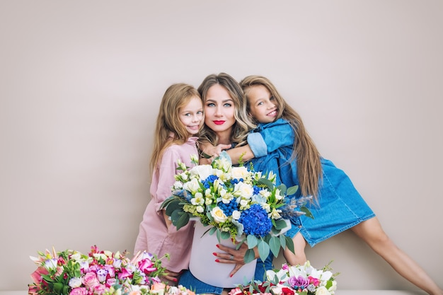 Happy family mother and two beautiful girls daughters on holiday in flowers together