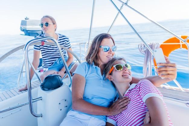 행복한 가족 - 사랑스러운 두 딸이 큰 요트에서 쉬고 셀카를 찍는 어머니