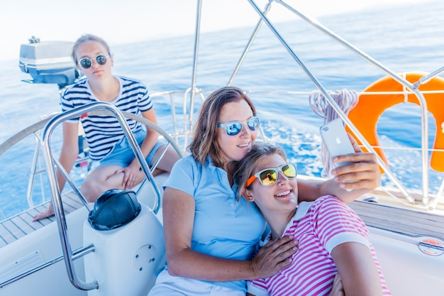 Happy family - mother with adorable two daughter resting and making selfie on a big yacht