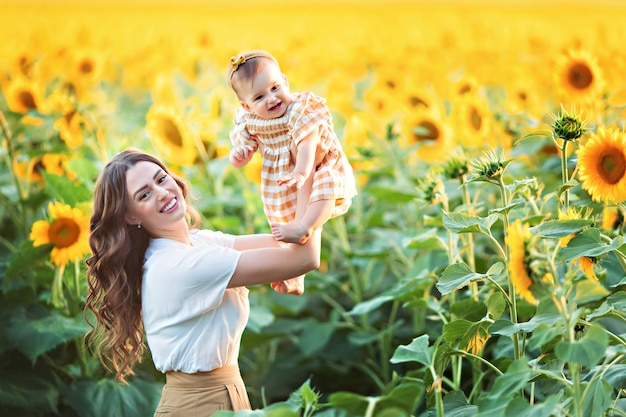 Happy family, mother with daughter play fun among blooming sunflowers outdoors