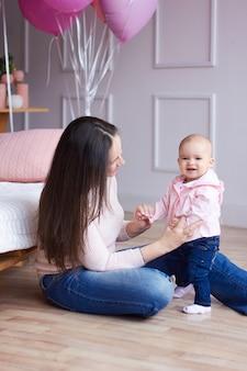 幸せな家族。明るいインテリアのlivihg部屋で彼女の小さな赤ちゃんと母親。贈り物や花で母の日のお祝い