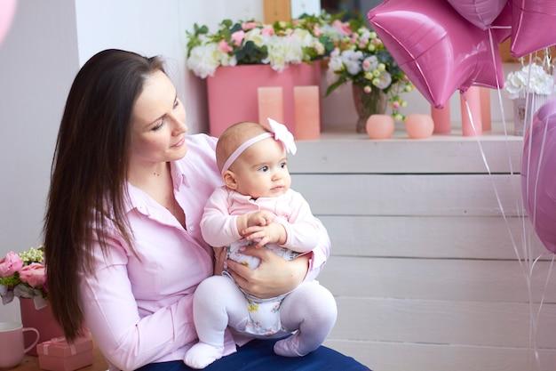 행복한 가족. 밝은 인테리어 livihg 방에서 그녀의 작은 아기와 어머니. 어머니의 날 축하 선물 및 꽃