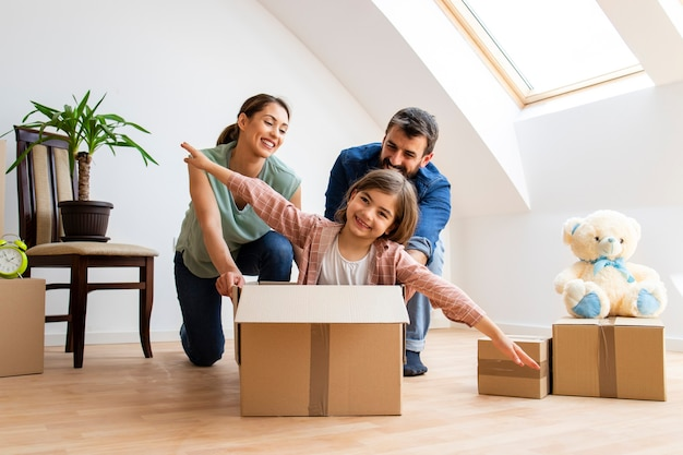 Happy family moving and riding in cardboard boxes at new home.