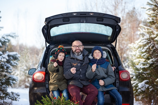 Happy family near black car at snowly winter day. concept holiday vacation.
