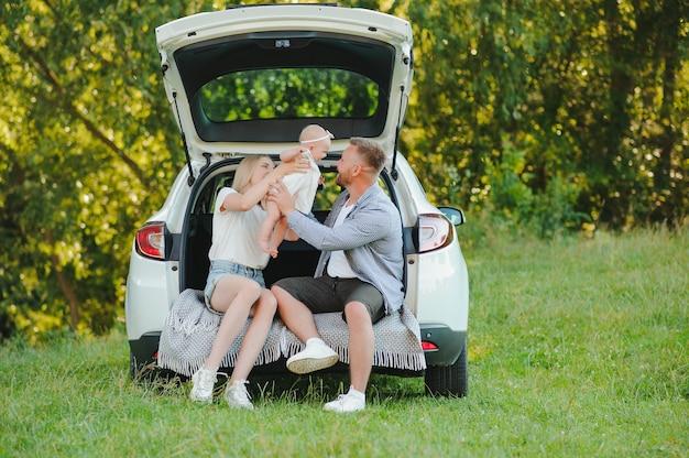 Счастливая семья возле багажника автомобиля в солнечный день. дорожное путешествие