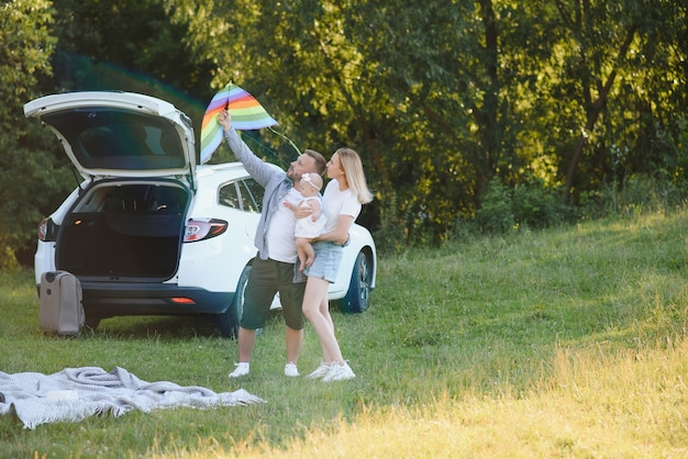 Happy family near car trunk on sunny day. road trip