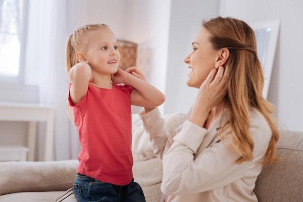 행복한 가족. 그녀의 딸과 함께 시간을 보내는 동안 웃고 행복 느낌 좋은 긍정적 인 즐거운 여자