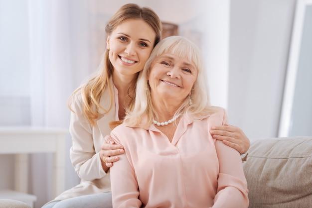 Счастливая семья. хорошая позитивная молодая женщина улыбается и смотрит на вас, обнимая свою мать