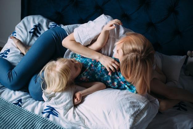 金髪のお母さんと娘の幸せな家族がベッドで遊んで楽しんでいます。