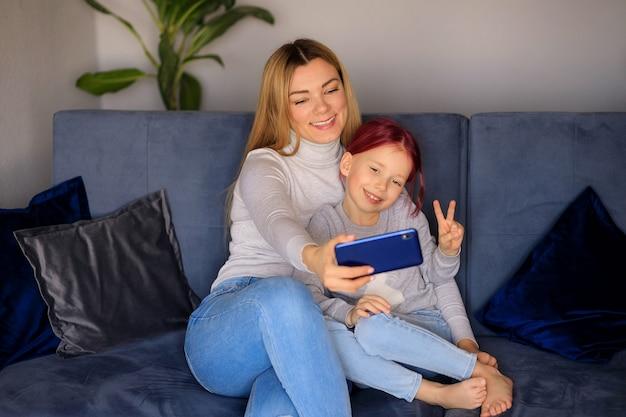 귀여운 작은 아이 딸의 행복한 가족은 소파에 부모 엄마의 무릎에 앉아 웃고 스마트 폰으로 즐겁게 지냅니다.