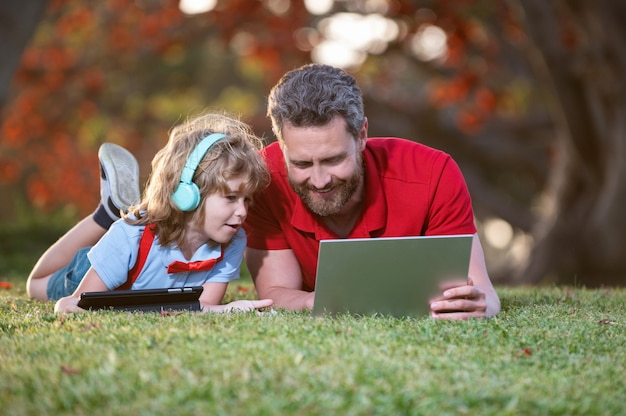 お父さんと息子の幸せな家族は、ビデオ通話やレッスンのためにラップトップを使用して、公園、教育でヘッドフォンで音楽を聴きます。