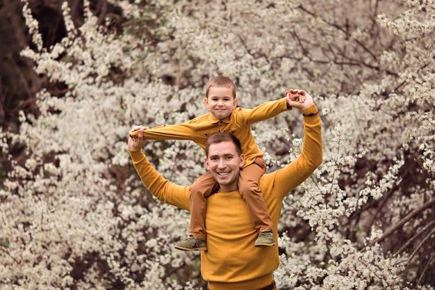 Счастливая семья отца и сына в цветущих деревьев.