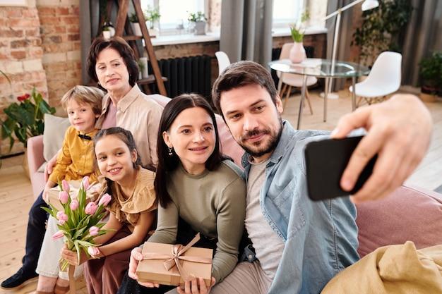 リビングルームの大きくて柔らかく快適なソファに並んで座って、自宅で自分撮りをしながらスマートフォンのカメラを見ている5人の幸せな家族