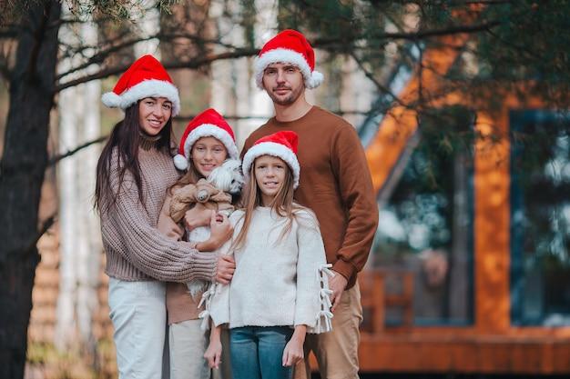 クリスマス休暇を楽しんでいる4人の幸せな家族。赤いサンタ帽子の子供を持つ親