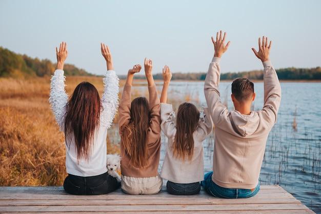 湖で秋の日に楽しんでいる4人の幸せな家族