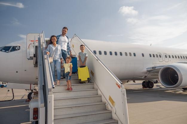 昼間に飛行機を降りる4人の幸せな家族。人、旅行、休暇の概念
