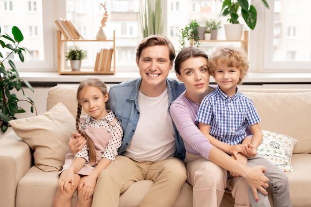 Счастливая семья из четырех человек в повседневной одежде сидит на диване в гостиной перед камерой и обнимается