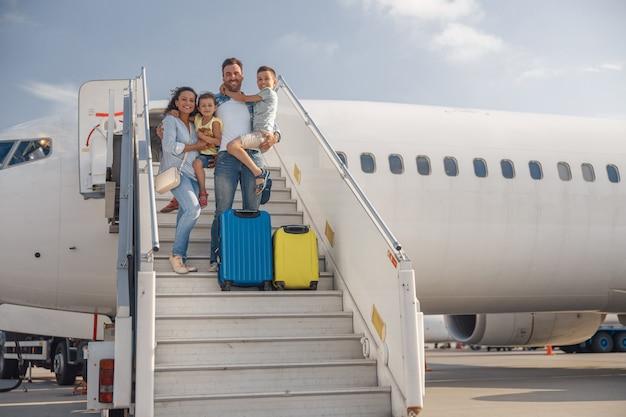 エアステアに立って、昼間に飛行機から降りる4人の幸せな家族。人、旅行、休暇の概念