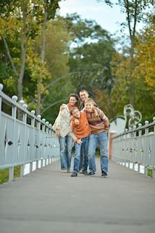 公園を歩いている4人の幸せな家族