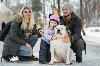 Happy family of mom, dad and little daughter pose with American bulldogs in the park