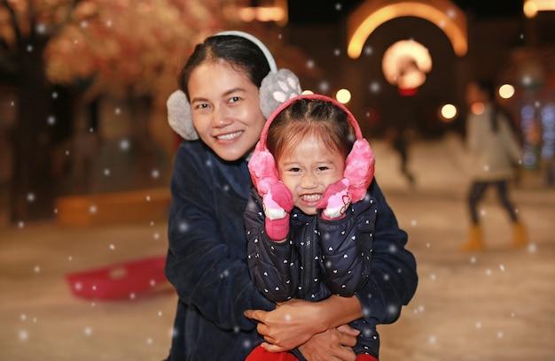 Счастливая семья матери и милая маленькая девочка весело провести время в снегу, зимнее время.