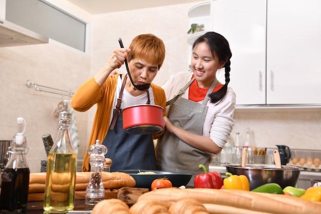 Счастливая семья матери и дочери, приготовление пищи на кухне, делая здоровую пищу вместе, чувствуя удовольствие
