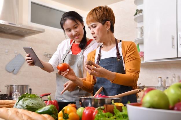 Счастливая семья матери и дочери с помощью цифрового планшета и приготовления пищи на кухне, делая здоровую пищу вместе, чувствуя удовольствие