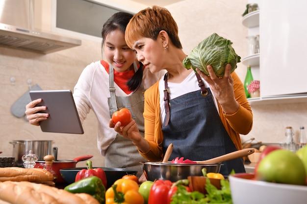 어머니와 딸의 행복 한 가족 디지털 태블릿을 사용하고 건강한 음식을 함께 만드는 부엌에서 요리 재미 느낌