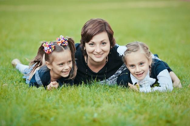 母と2人の娘の幸せな家族は、笑顔で公園の芝生の上で屋外で横になって楽しんでいます