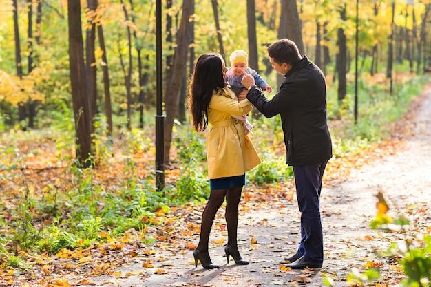 Счастливая семья матери, отца и ребенка в осенней природе