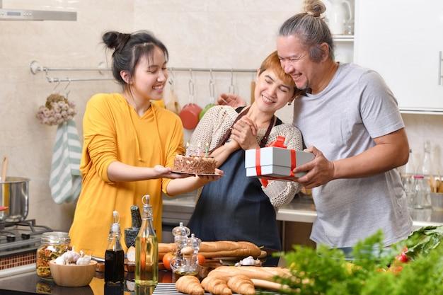 Счастливая семья матери, отца и дочери на кухне, празднование дня рождения вместе с тортом и подарком