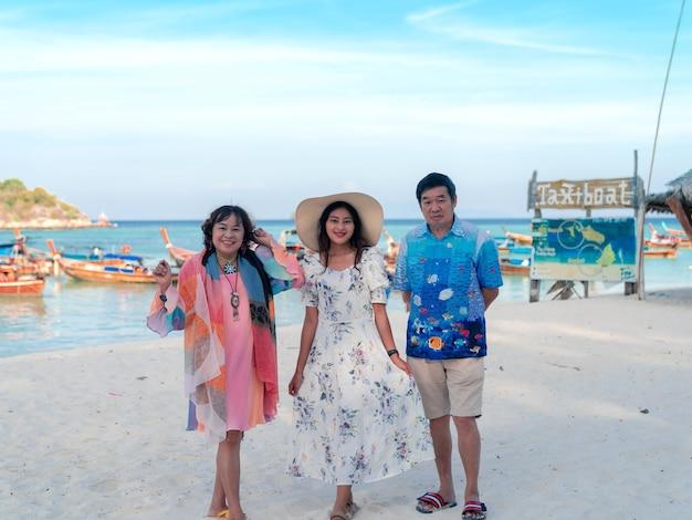 Счастливая семья старых родителей и взрослая дочь, стоящая вместе на песчаном пляже с видом на море с множеством длиннохвостых лодок-такси на островах липе, таиланд, синее море и небо, счастливое путешествие, отдых летом