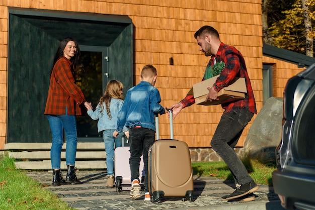 Счастливая семья родителей и двух детей несут чемоданы из машины в новый дом. концепция переезда.