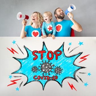 Счастливая семья супергероев кричит остановить covid по громкоговорителю