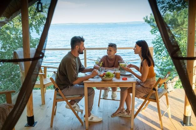 Счастливая семья из трех человек, обедающих за деревянным столом на террасе