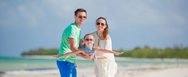 Счастливая семья из трех вместе веселиться на пляже
