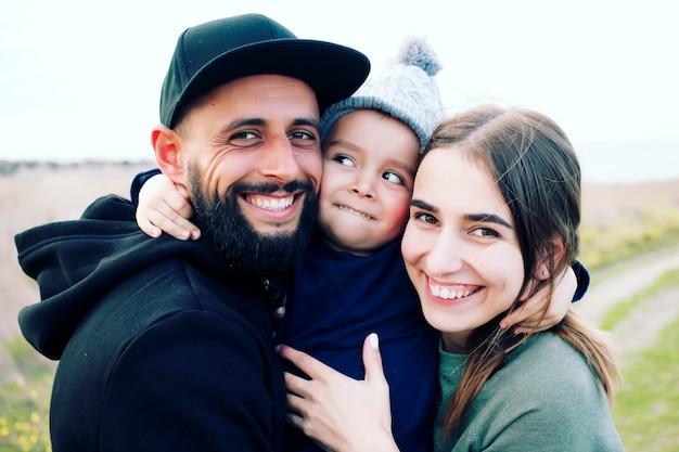 Счастливая семья из трех человек, весело проводящих время на открытом воздухе