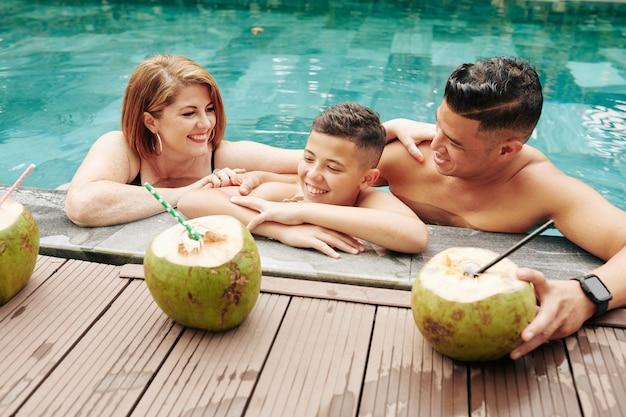 Счастливая семья из трех человек освежается в воде в солнечный летний день и пьет кокосовые коктейли