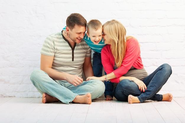 Счастливая семья из трех человек сидит на полу и смеется
