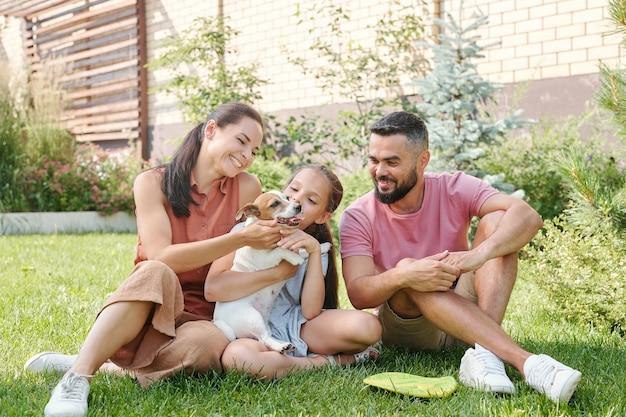 芝生の上に座って裏庭で彼らの小さな犬と一緒に時間を過ごす3人の幸せな家族