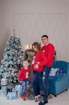 Счастливая семья из трех человек, молодая мать ожидает нового ребенка, отец и их маленький сын возле украшенной елки.