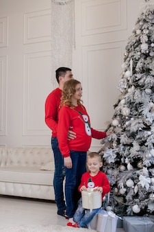 Счастливая семья из трех молодых мам, ожидающих нового ребенка, отца и их маленького сына рядом с украшенными