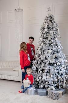 Счастливая семья из трех человек, молодая мать ожидает нового ребенка, отец и их маленький сын