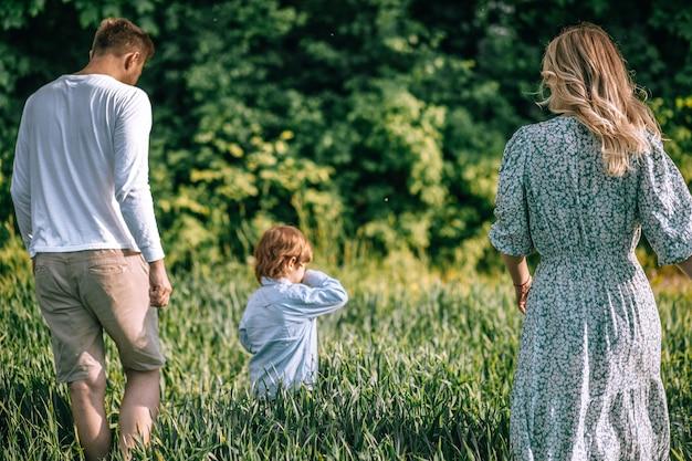Счастливая семья молодых фермеров и их сын гуляют в поле с пышной зеленой травой. вид сзади