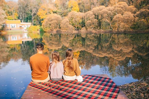 秋の公園でのピクニックで幸せな家族