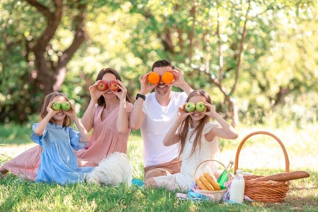 Счастливая семья на пикнике в парке в солнечный день