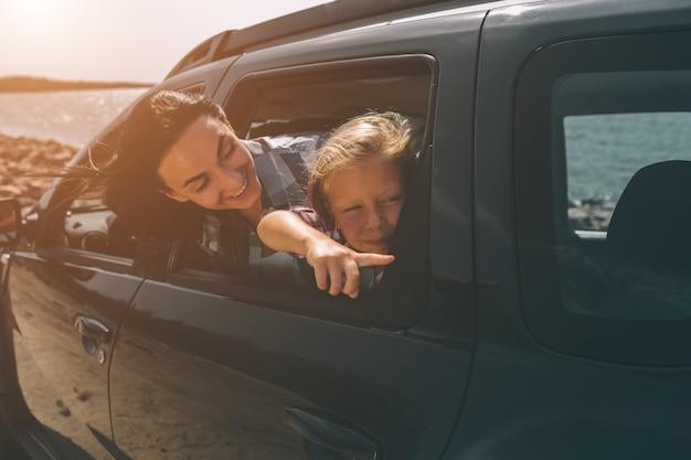 車での遠征で幸せな家族。お父さん、お母さん、娘は海や海、川で旅行しています。自動車による夏の乗り物