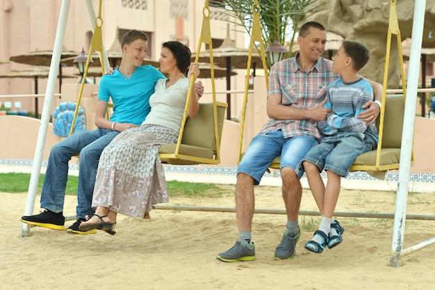 Счастливая семья на качелях летним вечером