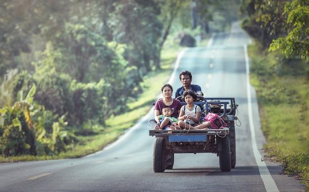 タイの北東部の道路上の車で幸せな家族