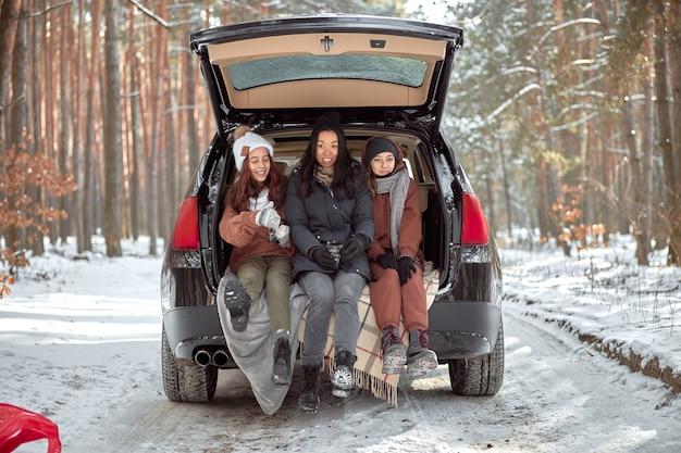 Счастливая семья на прогулке на открытом воздухе в солнечном зимнем лесу